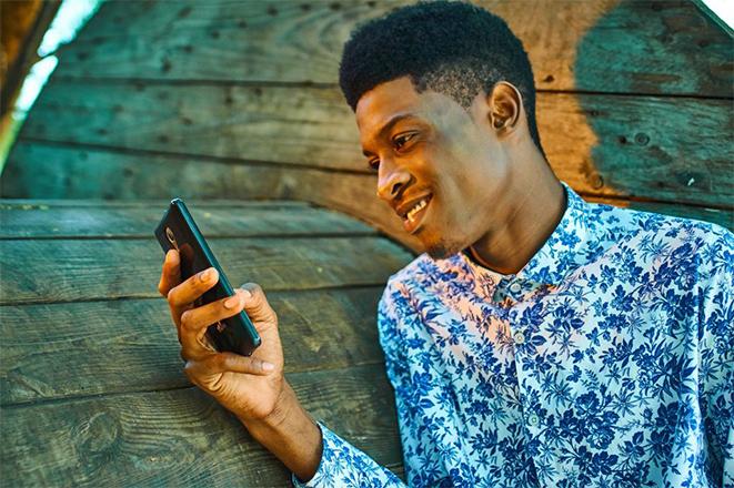 a man looking at his phone-  Zeevou