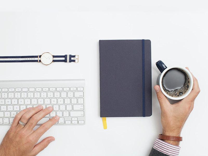 A keyboard and coffee, minimal working area- Airbnb Messaging Autoresponder- Airbnb Ranking - Zeevou