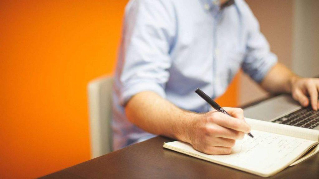A man writing business plan to Start a Vacation Rental Business- Zeevou